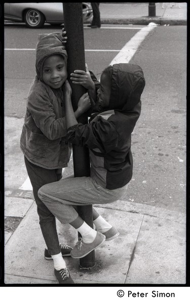 Two African American kids playing on a street corner, ca. 1968