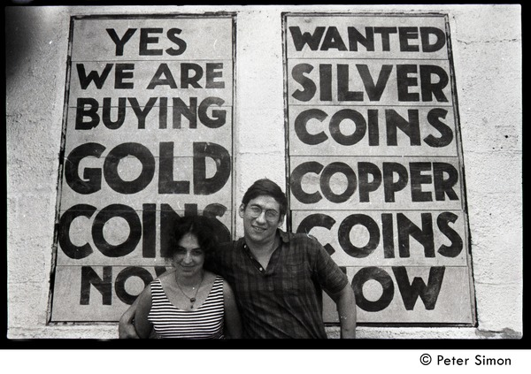 Lissa Matross and Harvey Wasserman standing in front of a sign at a curio store: 'Yes we are buying             gold coins...', ca. August 3, 1968