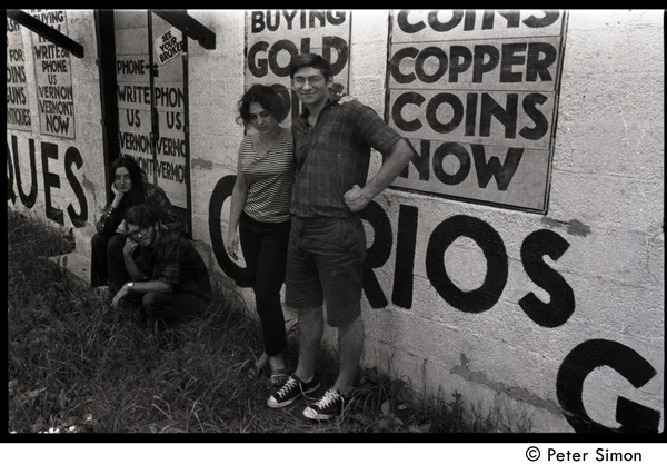 Communards standing in front of advertising signs at a curios store: Verandah             Porche, Michael Gies, Lissa Matross, and Harvey Wasserman (l. to r.), ca. August 3, 1968