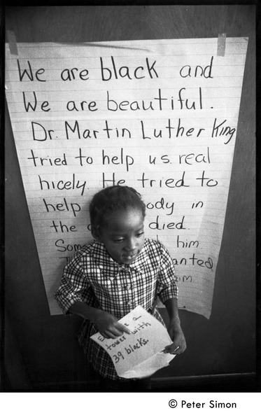 Young girl at the Liberation School, standing in front of a poster             honoring Martin Luther King: 'We are black and beautiful. Dr. Martin Luther King tried             to help us real nicely...', ca. September 30, 1968