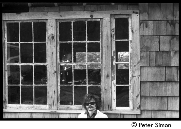 Laurie Dodge standing outside a house window, Packer Corners commune, ca. May 1, 1969
