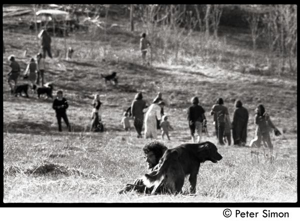 After the Maypole celebration, Packer Corners commune: leaving the field, with             Marshall Bloom lying in the foreground grass with a dog, ca. May 1, 1969