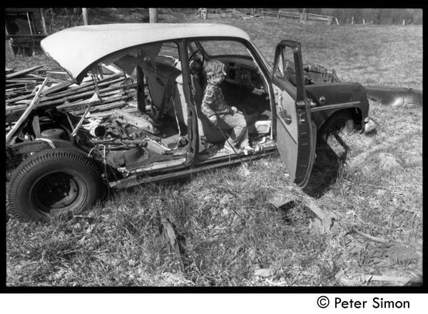 May Day at Packer Corners commune: child seated in a wrecked car, ca. May 1, 1969