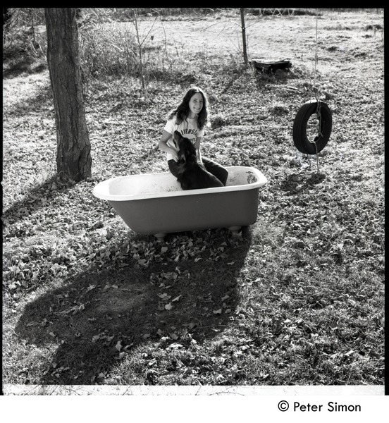 Jenny Rose seated in a tub outdoors with dog and tire swing, Tree Frog Farm Commune, 1970