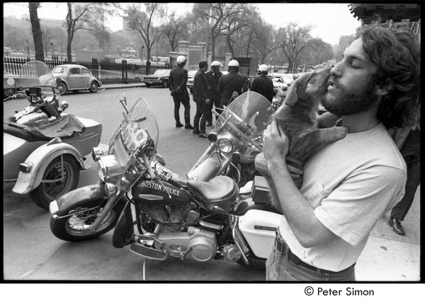 Elliot Blinder nuzzling a puppy and standing by parked Boston Police motorcycles, ca. May 5, 1970