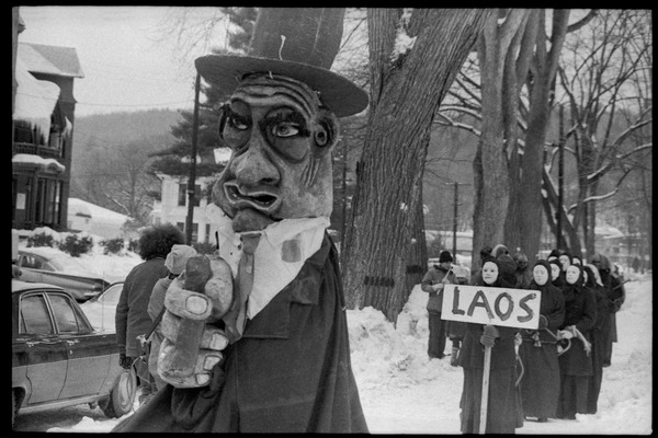 Bread and Puppet Theater protest against the invasion of Laos at the Vermont             State Capitol, with large puppet and group of cloaked and masked figures carrying a sign             reading 'Laos', February 10, 1971