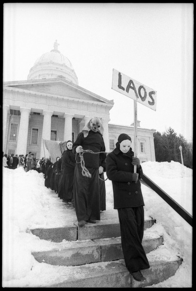 Bread and Puppet Theater descending the steps at the Vermont State House,             dressed in cloaks and masks and carrying a sign reading 'Laos' during a demonstration             against the invasion of Laos, February 10, 1971