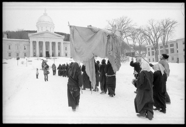 Protesters from Bread and Puppet Theater, dressed in cloaks and masks, unfurl a             banner or puppet during a demonstration against the invasion of Laos at the Vermont State House, February 10, 1971