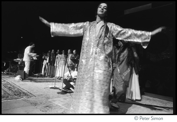 Woman dancing on stage at the Kohoutek Festival of Consciousness, with             unidentified musicians, ca. January 27, 1974