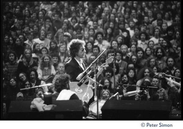 Bob Dylan performing on stage at the Boston Garden with The Band, Levon Helm on       drums in the foreground: View from rear stage looking over the performers and crowd: , ca. January 14, 1974