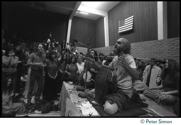Ram Dass playing drums on stage during an appearance at the College of Marin, ca. March 28, 1974