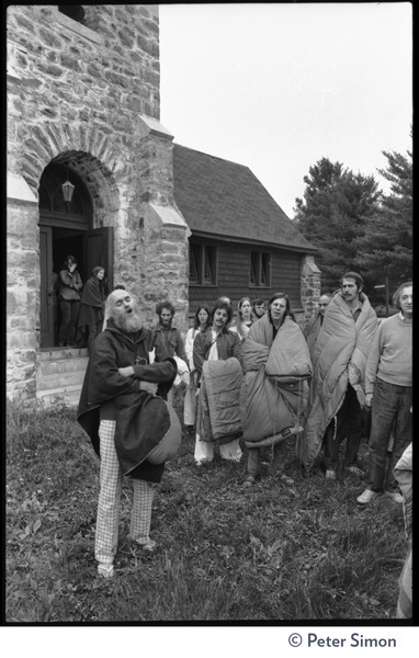 Ram Dass chanting outside the Reverend Preserved Smith Memorial Chapel, as             attendees file out wearing blankets, Rowe Center spiritual retreat, ca. May 26, 1975