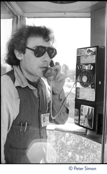 Charles Light (wearing a press pass for Green Mountain Post Films) using a pay phone, ca. April 30, 1977