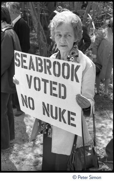 Local resident (an older woman) holds up a sign reading 'Seabrook voted no nuke' at the occupation of Seabrook Nuclear Power Plant, ca. April 30, 1977