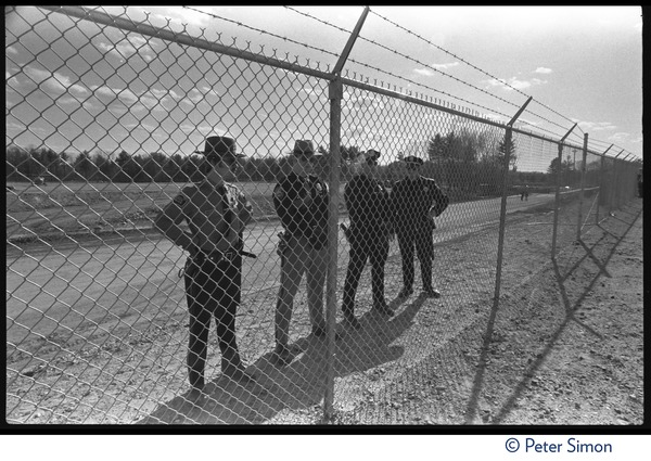 Line of police behind a chainlink fence during the occupation of Seabrook Nuclear Power Plant, ca. April 30, 1977