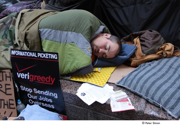 Occupy Wall Street: man sleeping by sign reading, 'verigreedy, stop sending our jobs oversees', December 1, 2011