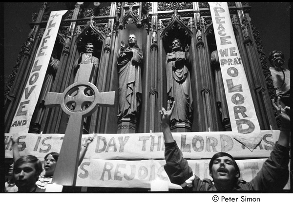 Sanctuary movement and occupation of Marsh Chapel: protestors on chapel altar flashing peace sign, October 5, 1968