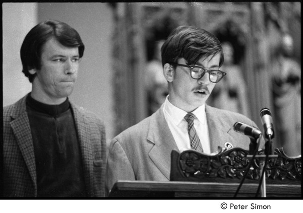 Sanctuary movement and occupation of Marsh Chapel: Raymond Kroll, deserter taking sanctuary in chapel, speaking at microphone with an unidentified priest in the background, October 5, 1968