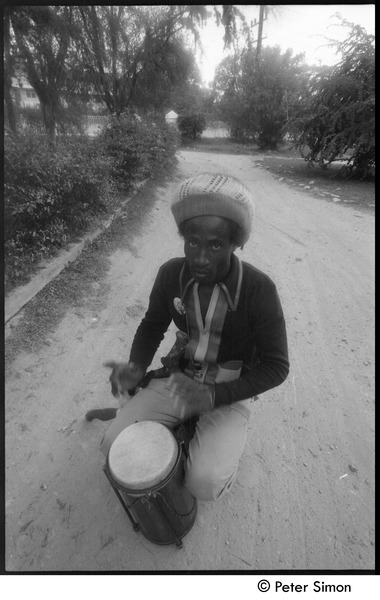 Man squatting in a dirt driveway playing a funde, ca. 1976