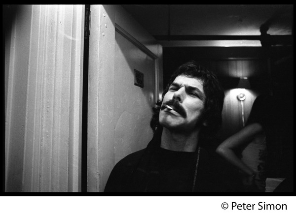 Mickey Hart, smoking a cigarette, standing by the crew room door, ca. 1977
