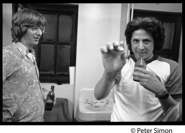 Phil Lesh with unidentified man holding a bottle cap, ca. 1977