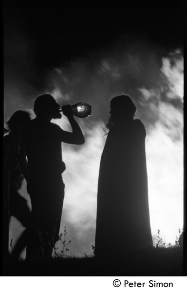 After the Maypole celebration, Packer Corners commune: silhouette and bonfire,             with man drinking wine from a bottle, ca. May 1, 1969