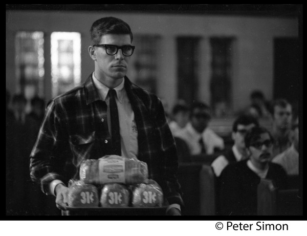 Sanctuary movement and occupation of Marsh Chapel, Boston University: Student bringing loaves of bread into the Chapel: , ca. October 5, 1968