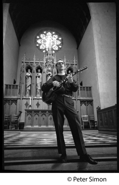 Sanctuary movement and occupation of Marsh Chapel, Boston University: Young priest playing the guitar in front of the altar: , ca. October 5, 1968