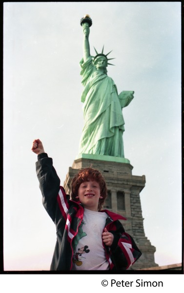 Statue of Liberty: view from the front, with child, raised fist, standing in             foreground, ca. 1990