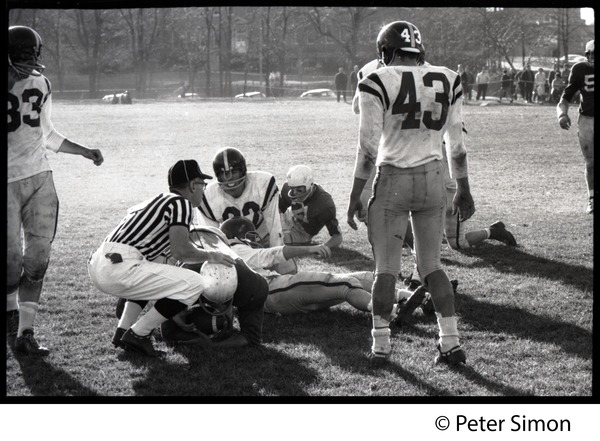 Referee kneeling over an injured football player while others look on, ca. 1967