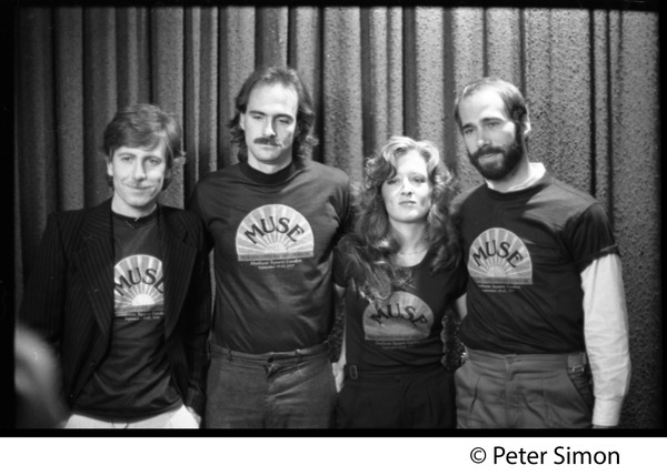 Musicians United for Safe Energy concert performers: Graham Nash, James Taylor, Bonnie Raitt, and John Hall             (l. to r.) wearing MUSE tee-shirts, ca. September 1979