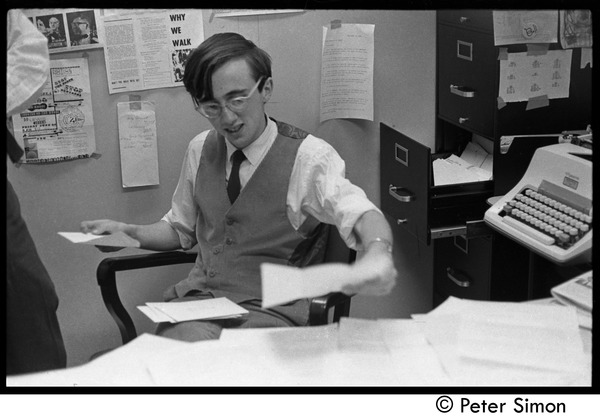Raymond Mungo seated at his desk at the Boston University News Office, ca. 1967