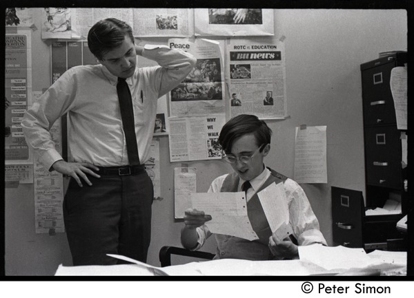 Raymond Mungo reading a letter while seated at his desk at the Boston University News Office, with Joe             Pilati looking on, ca. 1967