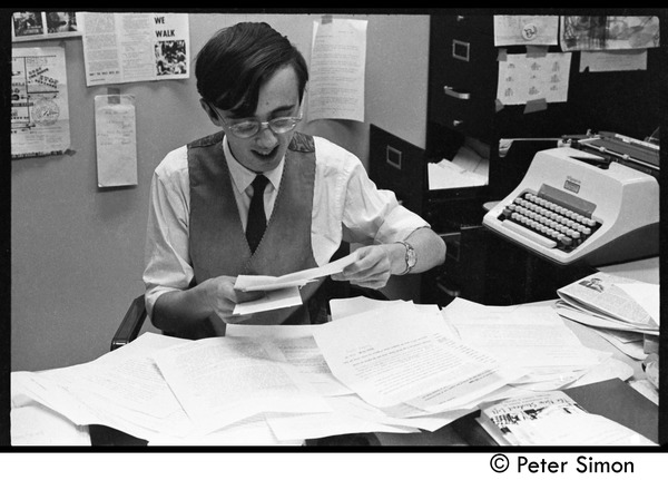 Raymond Mungo reading, seated at his desk at the Boston University News Office, ca. 1967