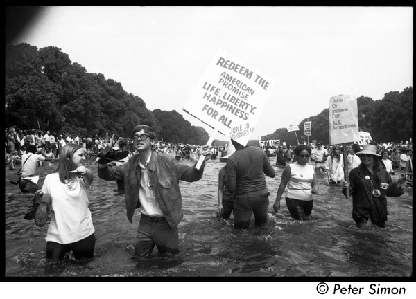 "Splashing in the Reflecting Pond during the Poor Peoples' Campaign Solidarity Day: Protesters holding signs reading 'Redeem the American promise, life, liberty,         happiness for all Jun 19 Solidarity Day"" and 'Jobs or income for all Americans': , ca. June 19, 1968"