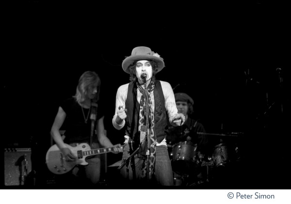 Bob Dylan performing at the Harvard Square Theater, Cambridge, with the             Rolling Thunder Revue: Mick Ronson (guitar) and Howie Wyeth (drums) in the background: , November 20, 1975