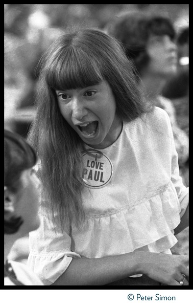 Manic Beatles fans during concert at Shea Stadium: Young girl wearing an 'I love Paul' button: , August 15, 1965