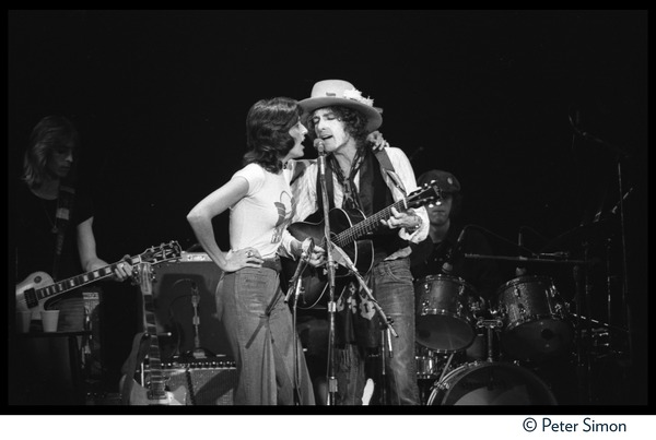 Joan Baez with arm on the shoulder of Bob Dylan, performing with the Rolling             Thunder Revue at the Harvard Square Theater, ca. November 20, 1975