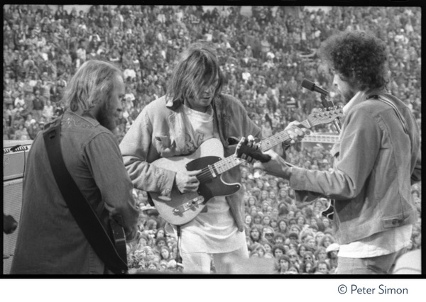 Bob Dylan performing with the Band and Neil Young at Bill Graham's SNACK             (Students Need Athletics, Culture and Kicks) benefit concert, Kezar Stadium: From left: unidentified guitarist, Neil Young, Bob Dylan: , ca. March 1975