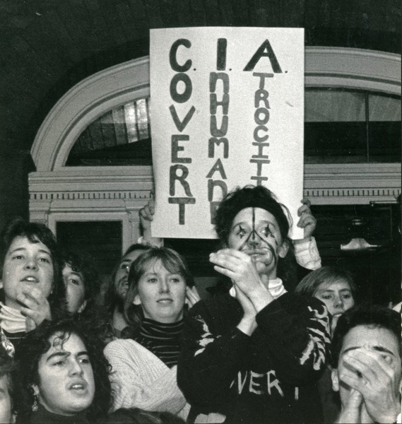 Student occupation of Munson Hall, UMass Amherst, with banner reading 'Covert Inhuman Atrocities', ca. November 1986