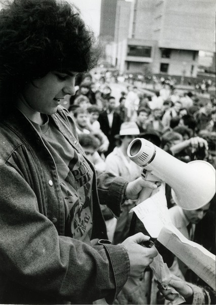 'Students protest': speaker in front of crowd at UMass Amherst holding bullhorn, wearing t-shirt             reading 'Put the CIA on trial', ca. November 1986