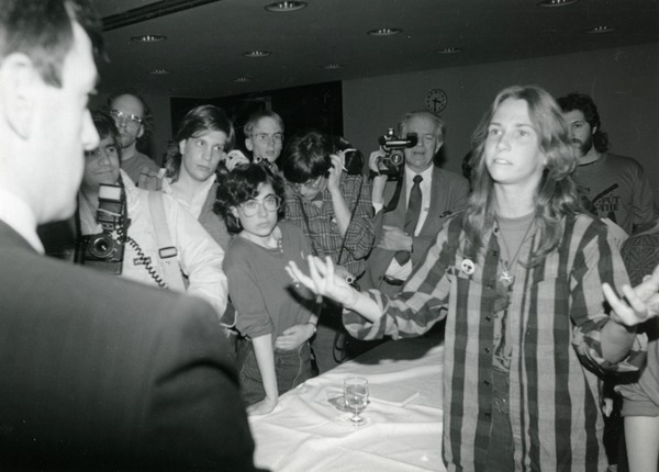Unidentified woman talking with a man as crowd looks on, probably at student             takeover of forum at UMass Amherst, ca. April 1987