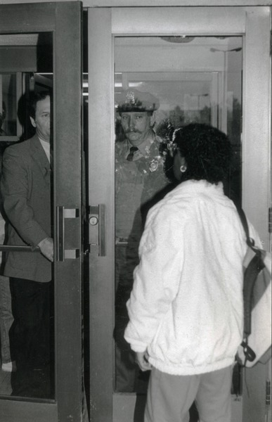 Woman greeted at door of Whitmore Hall, UMass Amherst, by police officer and official, ca. 1986