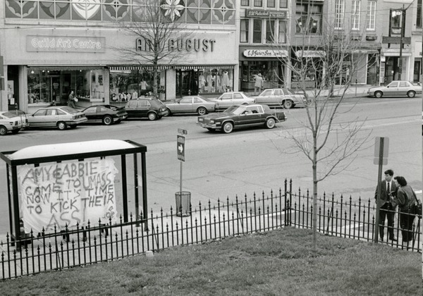 Banner on bus kiosk in Northampton, reading 'Amy & Abbie came to UMass now it's time to kick their ass!', ca. April 1987