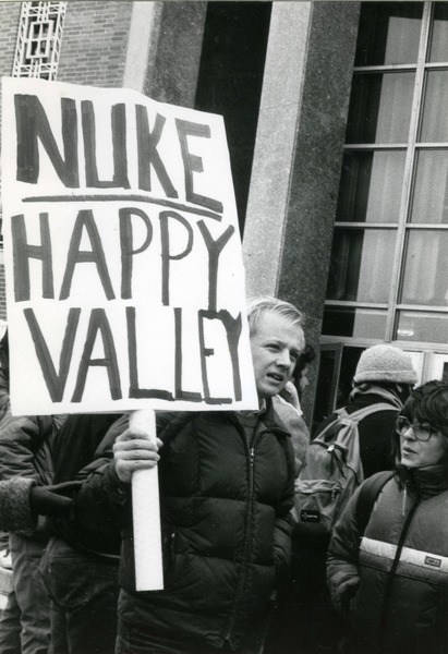 Right wing protester at UMass Amherst with placard reading 'Nuke Happy Valley', ca. April 1987