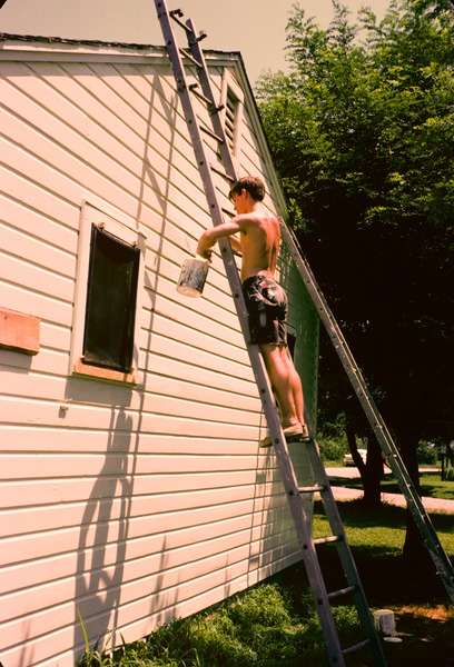 Unidentified shirtless male volunteer painting a house on a