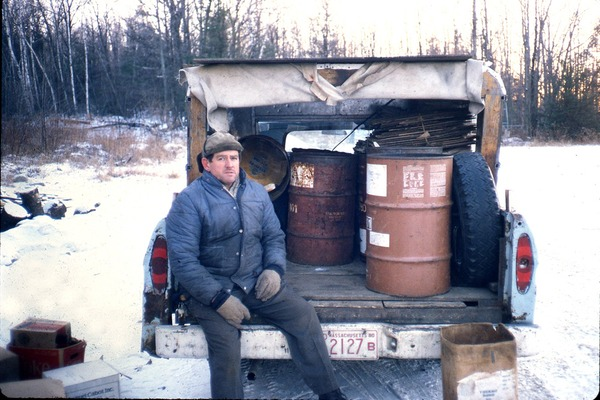 Wendell Bicentennial slide show: Man seated on the back of a pickup truck carrying 55 gallon drums: , ca. 1981