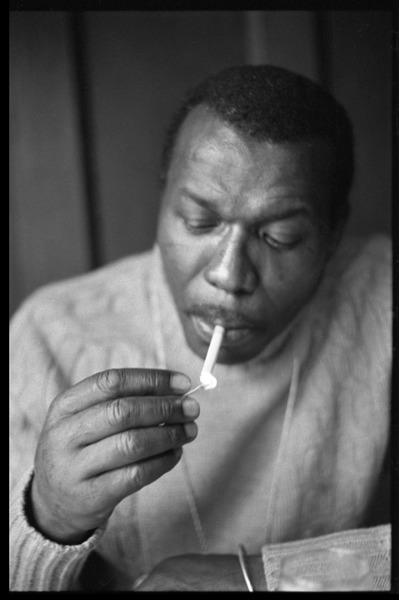 Elvin Jones: half-length portrait of jazz musician, seated, lighting a cigarette, ca. January 1973