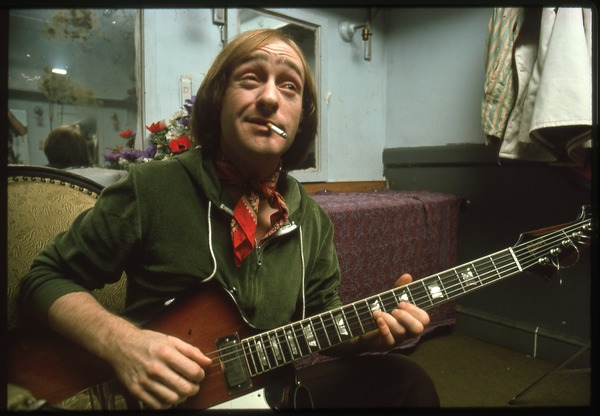 Dave Mason backstage playing guitar and smoking a cigarette, 1975