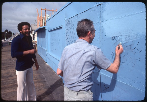 Bill Withers: Withers laughing with a man cleaning graffiti, 1975
